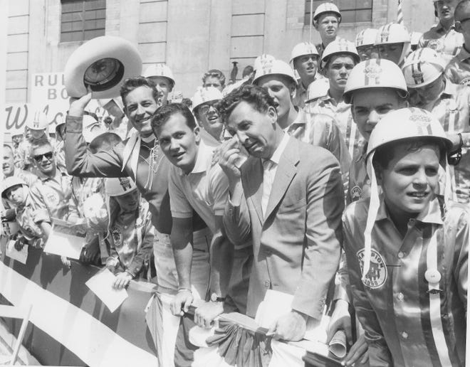 Singer Pat Boone leans on a rail between Western star Guy Madison and comic actor Eddie Bracken while watching the All-American Soap Box Derby with young racers Aug. 17, 1958, in Akron.