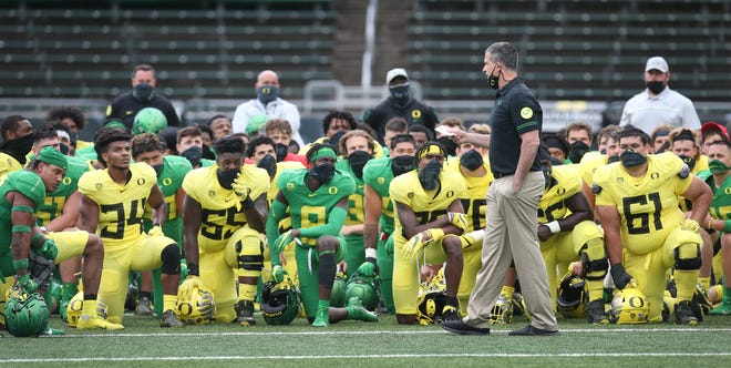 """Oregon coach Mario Cristobal talks to his players after the Ducks' spring game in May. The Ducks have produced 13 NFL draft picks over the last three years. """"It's a collective effort really. We take a lot of pride in that,"""" he said. """"Yeah, you're upping the talent level that's coming in, but you're also just pouring yourself into player development. It's showing up and it's showing up big."""""""