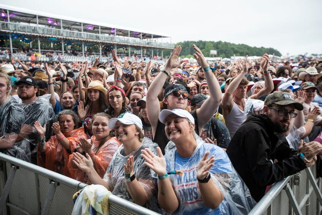 Country music fans cheer on Friday as they wait for Chris Lane at the main stage during the Faster Horses Festival at Michigan International Speedway in Cambridge Township.