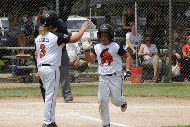 Tecumseh Americans' Andon Ondrovick, right, high-fives teammate Ian Lajiness (3) after scoring during the second inning of the team's 8-9-10 District 16 championship game against Plymouth Canton on Saturday at Mitchell Park