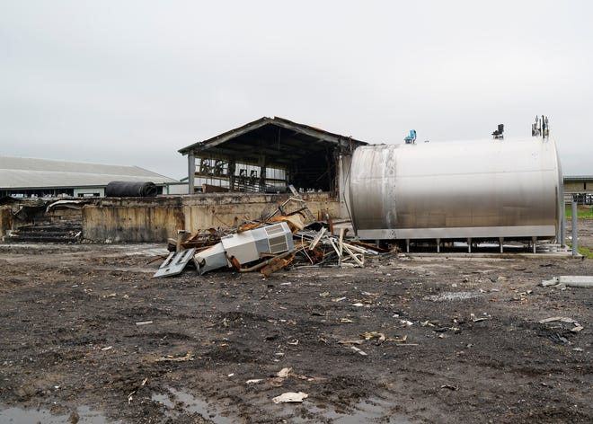 The stainless steel milking tanks remain standing outside of the destroyed milking barn Saturday at Hoffland Dairy near Clayton. A fire destroyed the milking barn July 5.