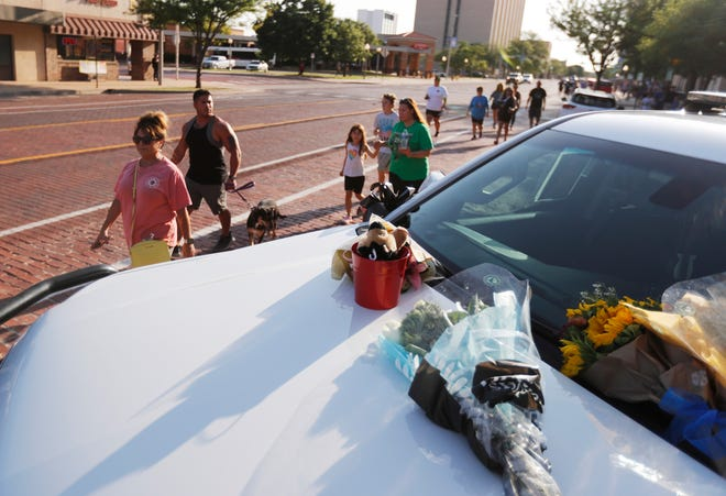 Walkers walk past a Sheriff's cruiser with memorials during a one mile walk Friday in the memory of Lubbock County Sheriff's Office Sgt. Josh Bartlett, who was killed while serving a warrant in Levelland Thursday. The walk took place Friday, July 16, 2021at the Lubbock County Sheriff's Office law Enforcement Center.