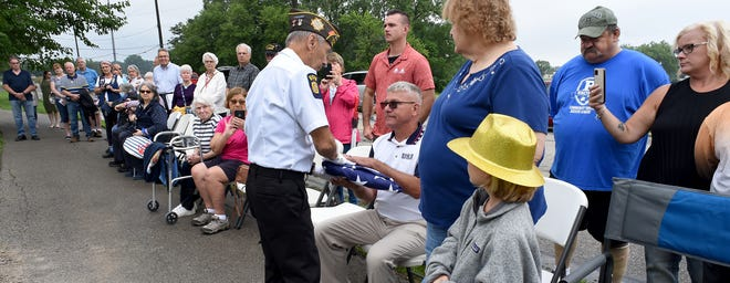 Jim Liedel of the Veterans of Foreign Wars, Monroe Post 1138, honor guard presents the American flag to Randy Pitcher in honor of his mother Lucienne (Lucy) Reh Pitcher. The Memorial Bench Ceremony was held at the River Raisin National Battlefield Park in Monroe Saturday.