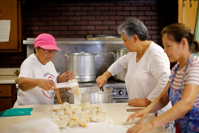 Olivia Dennard, Rosalinda Murillo and Maria Fraire take tamales out of a pot after cooking them at Santa Maria Virgen Episcopal Church in Oklahoma City.