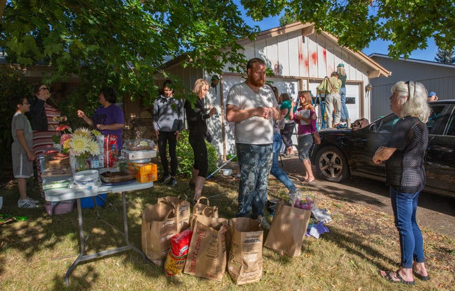 Ben Christensen, center, talks with neighbors who brought food, buckets, ladders, tools and cleaning supplies to help Christensen and his wife, Xia Wang, clean nearly 30 paintballs splatters on their house and cars Friday, July 16, 2021.