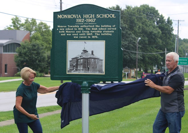 Linda (Shields) Kaiser and Monroe Township Trustee Mike Marsh uncover a historical plaque on Saturday. Both were members of the last class to graduate from the old Monrovia High School building.