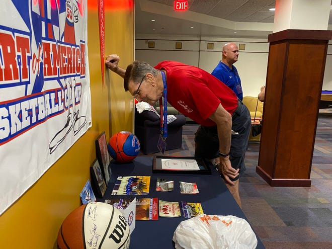 Former Heart of America Basketball Camps director and CEO Bob Murray looks over memories during a reception Thursday at Kansas Wesleyan University.