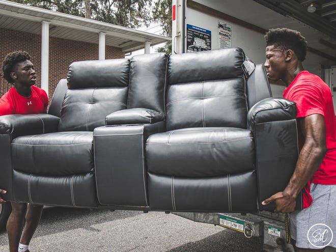 Buchholz running back Quan Lee, right, and his cousin, Artrayul Goss, at a recent job for ACE Moving Company.