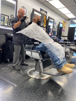 Joe Strollo cuts the hair of 17-year customer Joey Sanchez in his Barstow barber shop on Wednesday, July 14, 2021.