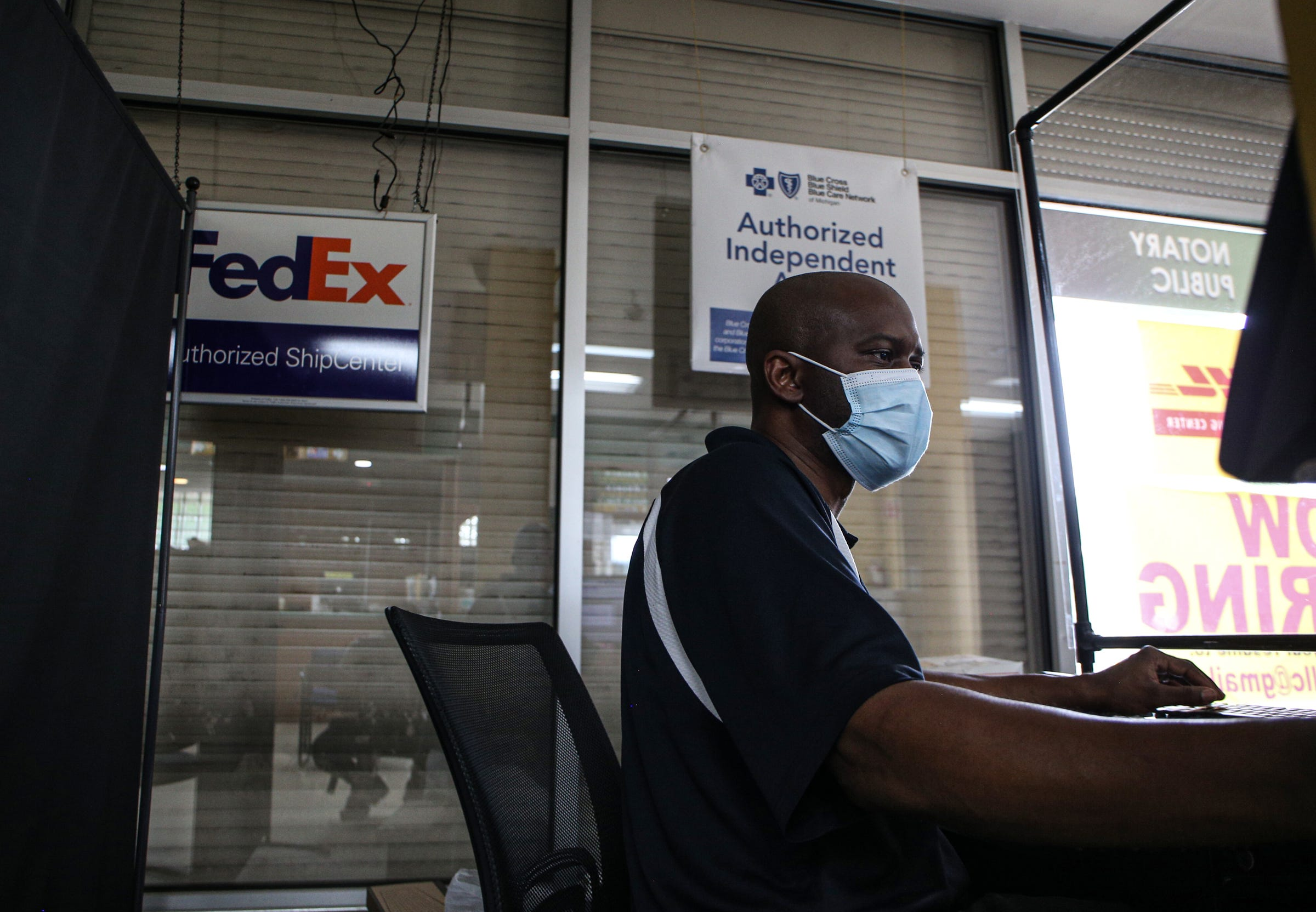 Mario Hall helps a customer at Hallstarz Business Center in Detroit on July 15, 2021. The business center is a one-stop-shop in the Bagley neighborhood. A neighborhood source for packing, shipping, printing and other business services. Created 36 years ago by a Detroit couple, Milton Hall Jr. and Vanessa Hall. The business is now run by their oldest son, Mario Hall with help from his five brothers.