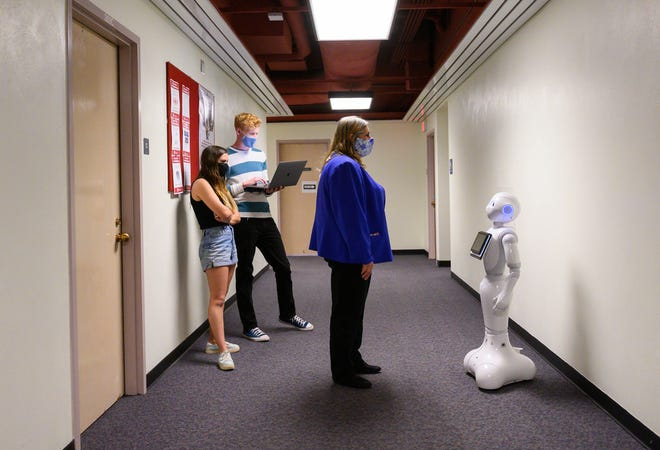 Betsy Stringam, right, professor of hotel, restaurant and tourism management at New Mexico State University, talks with Pepper the robot, while graduate students Rebecca Skulsky, left, and Harrison Preusse watch the interaction.