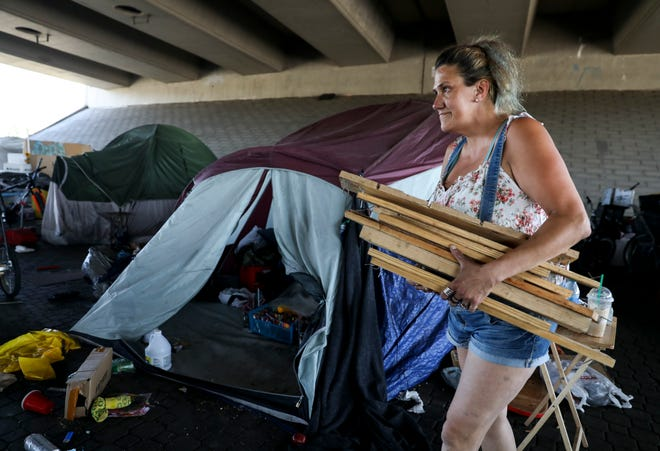 Carla Cheuvront gathers her belongings as she prepares to move out of a homeless encampment near Market Street NE before it is cleared on Saturday, July 17, 2021 in Salem. Crews will begin sweeping the area on Monday.