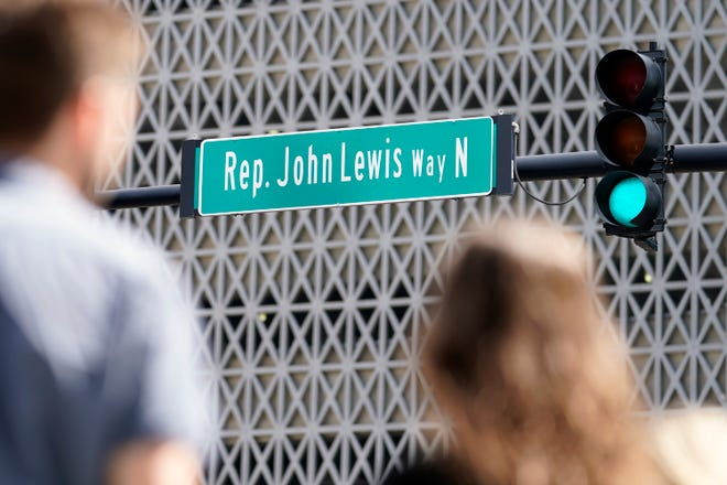 People wait to cross a street that was renamed to honor former Rep. John Lewis Friday, July 16, 2021, in Nashville, Tenn.