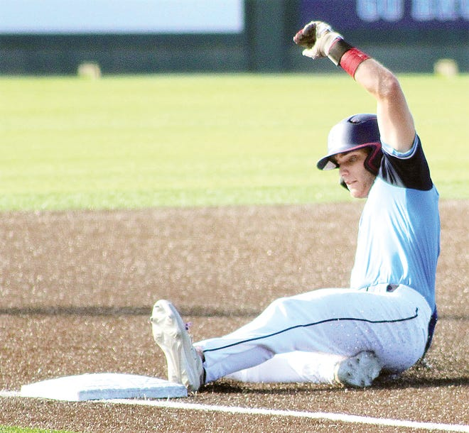 A Bartlesville Doenges Ford Indians' baserunner takes custody of third base during recent baseball action at Custer Stadium.
