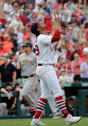St. Louis Cardinals closing pitcher Alex Reyes, foreground, points skyward after finishing off the San Francisco Giants as Giants' Alex Dickerson, back left, rounds third base in the ninth inning of a baseball game, Sunday, July 18, 2021, in St. Louis.