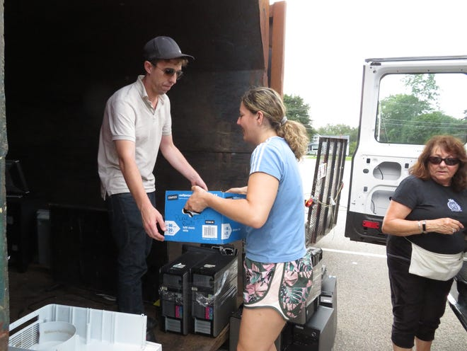 Nico Chanut and Allison Wood accept computers, keyboards and other electronic items during a recycling event at St. Mark's in Sutton on July 17.