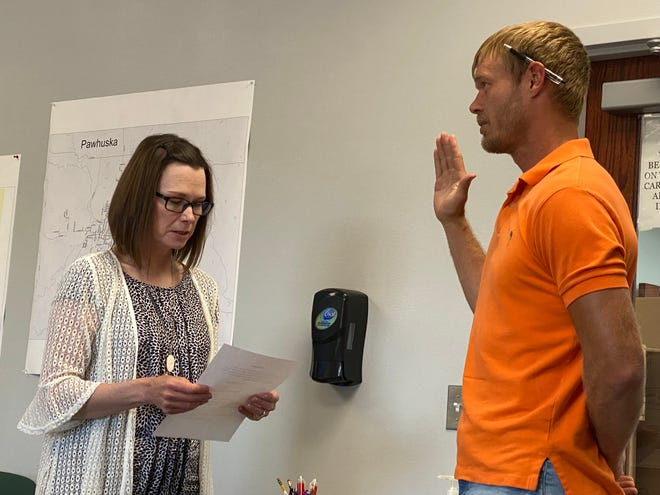 """Craig Walker, right, takes the oath of office Monday night, July 12, to become the newest member of the Pawhuska Board of Education. Walker filled a seat that became vacant due to the resignation of Addie Roanhorse. Walker said he views Board of Education service as a """"broad picture"""" opportunity to """"make subtle differences that end up being large differences down the road."""""""