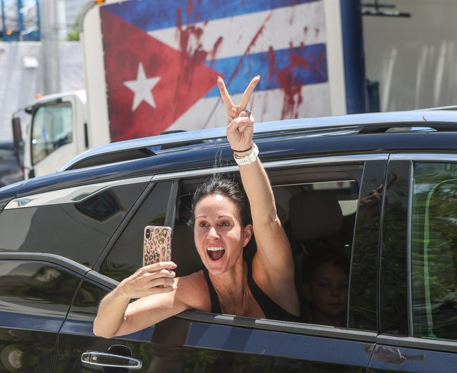 A woman screams out her window in support of people at West Palm Beach City Hall taking part in a July 18 rally to support anti-government protesters in Cuba.