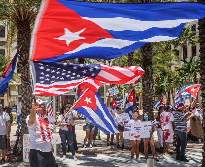 People take part in a rally Sunday outside West Palm Beach City Hall to support anti-government protesters in Cuba.