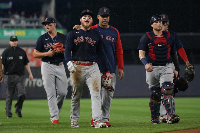Red Sox left fielder Alex Verdugo (99) is walked off the field by manager Alex Cora (13) after a fan threw a baseball at him during the sixth inning against the New York Yankees at Yankee Stadium on Saturday night.
