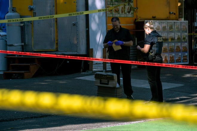 Police investigate an overnight shooting Saturday, July 17, 2021 near a pod of food trucks in a popular pedestrian area in downtown Portland. Police said one person died and at least six people were injured in that early morning shooting Saturday in Portland.