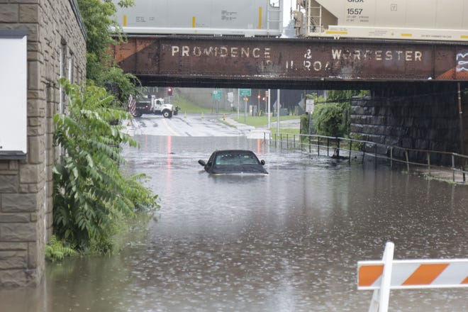 A car is submerged in flash floodwaters under a railroad bridge on Cambridge at Kansas streets during Saturday's torrential rain.