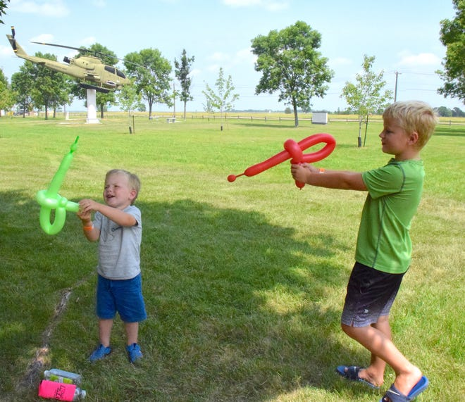 Brothers Dolton, left, and Carter Brennan pretend play with their space weapons during Cookin' on Kampeska.