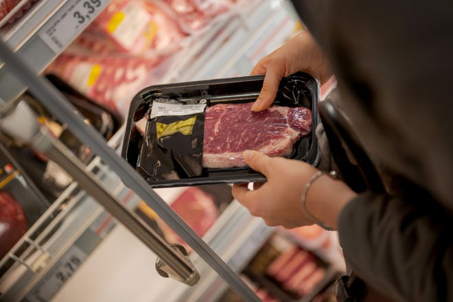 Woman buying beef at supermarket