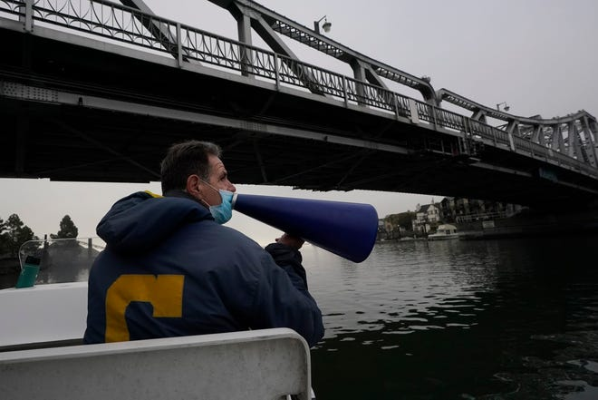 Coach Mike Teti speaks into a megaphone toward rowers practicing in the Oakland Estuary in Oakland, Calif., on Nov. 19, 2020.