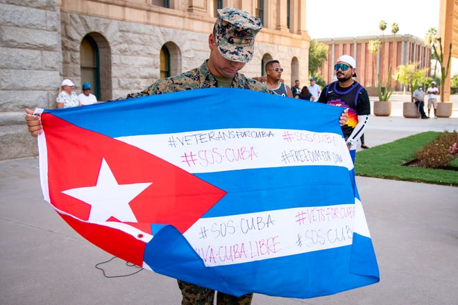 Richard Diaz Labrada shows off a Cuban flag emblazoned with messages advocating to free Cuba on July 17, 2021.