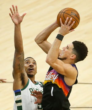 July 17, 2021; Phoenix, Arizona, USA; Suns' Devin Booker (1) shoots against Bucks' Jeff Teague (5) during the first quarter in Phoenix. Patrick Breen-The Republic