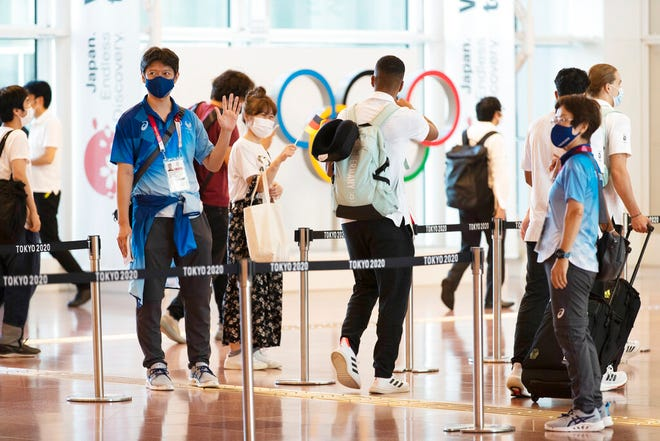 Tokyo 2020 staff members welcome German team members for the Tokyo 2020 Summer Olympic and Paralympic Games as they arrive at Haneda international airport in Tokyo on Sunday, July 18, 2021. (AP Photo/Hiro Komae)