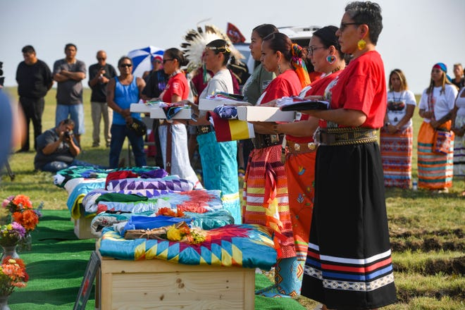 Members of the tribal color guard hold an American flag, a prayer flag and the Rosebud Sioux tribal flag for relatives of the Rosebud Sioux children returned home 142 years after their deaths on Saturday, July 17, 2021 at the Rosebud Sioux Tribe Veterans Cemetery.