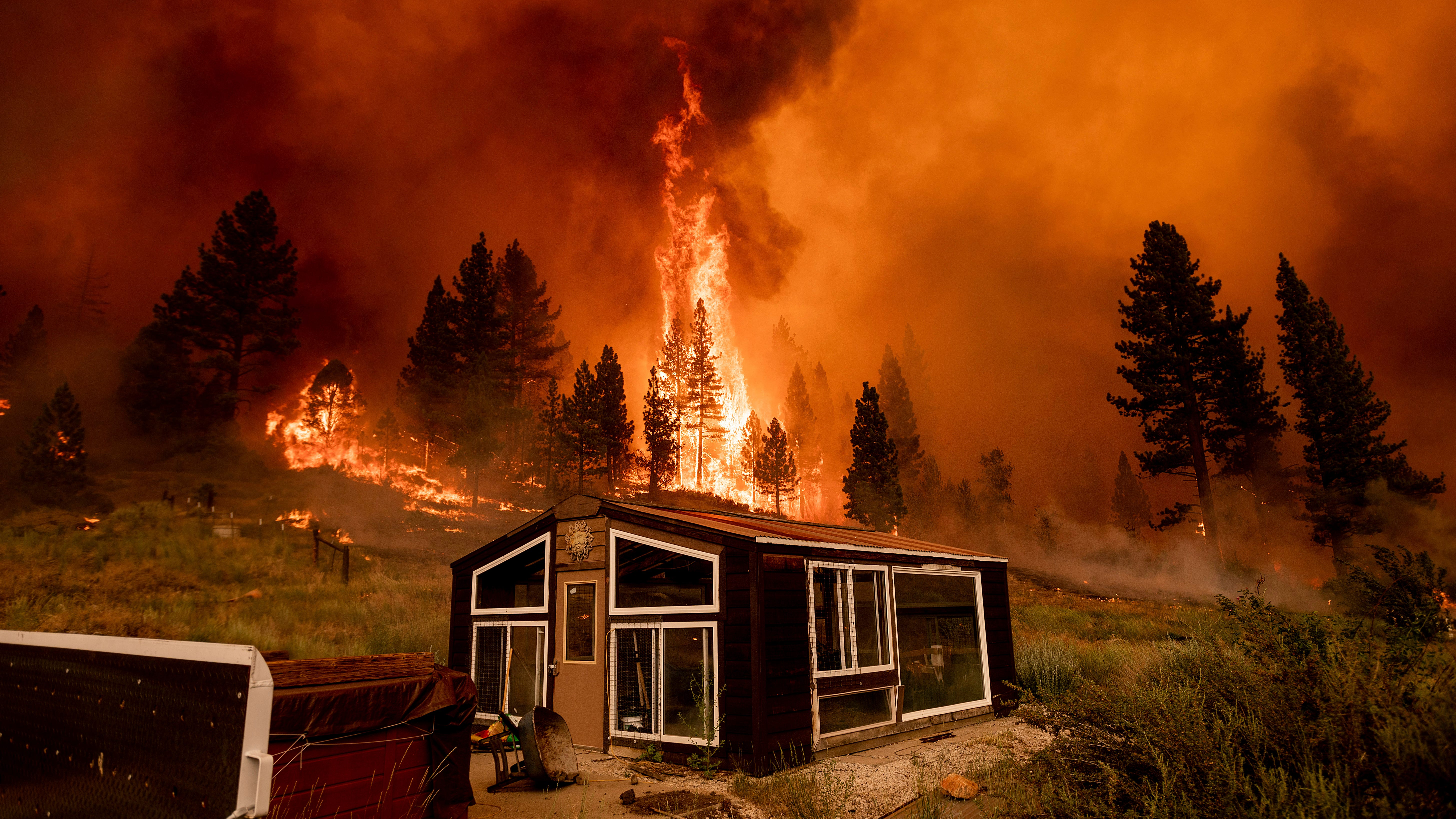 The Tamarack Fire burns behind a greenhouse in the Markleeville community of Alpine County, Calif., on Saturday, July 17, 2021.