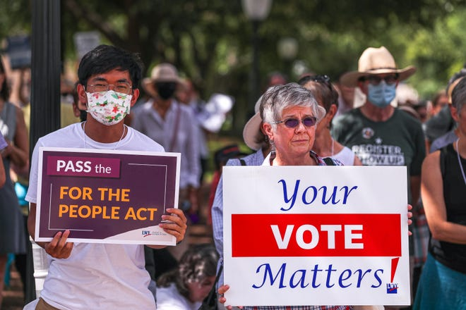 """Marguerite Scott, right, and Andy Hsieh, left, hold signs at a voting rights rally on the south steps of the Texas Capitol on July 19, 2021. About 200 activists attended a """"Let My People Vote,"""" rally to urge Texas lawmakers to rethink restrictive new voting laws."""