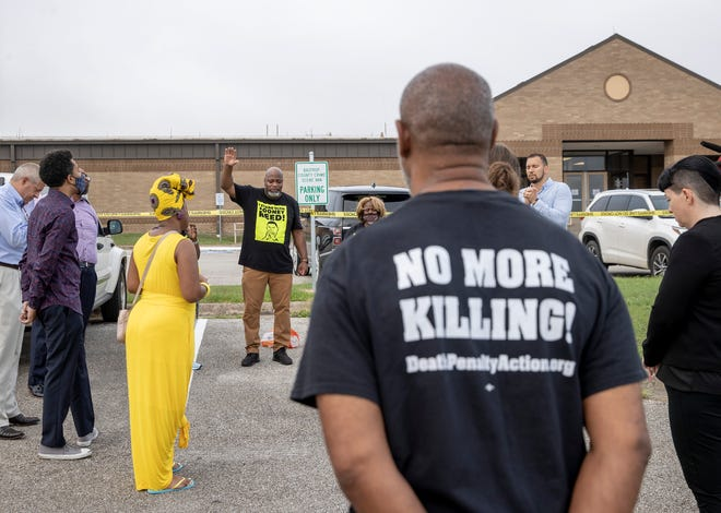 The Rev. Sherwynn Patton, hand raised, leads a prayer with supporters of Rodney Reed outside the Bastrop County Justice Center on Monday before a hearing for the death row inmate in which his lawyers tried to prove his innocence.