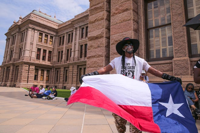 """Ashton Smith holds a Texas flag at a July 19 rally outside of the Texas Capitol. About 200 activists attended a """"Let My People Vote"""" rally to urge Texas lawmakers to rethink restrictive new voting laws. [AMERICAN-STATESMAN/FILE]"""