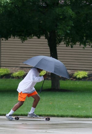 Justice Buckner doesn't let a little rain stop him from riding his long board in the cul de sac near his home last summer in Copley. This July could end up the 10th-wettest on record.