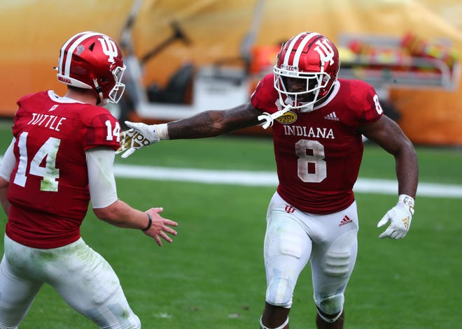 Indiana running back Stevie Scott celebrates a touchdown with quarterback Jack Tuttle during last year's Outback Bowl loss to Ole Miss. Scott, a three-year starter, has moved on to the NFL and Tuttle, who took over when Michael Penix Jr. went down with a knee injury in the fifth game, will revert back to backup.