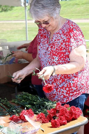 Jan Fasone helps prepare a bunch of carnations for sale July 31, 2019, for the 60th Greater Alliance Carnation Festival at Carnation City Mall.