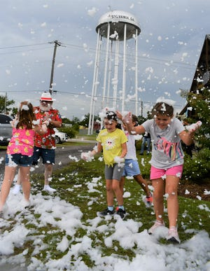 """With the Sylvania water tower in the background, """"Vacation Santa"""" and local children play in the """"snow"""" created by detergent foam at the Market on Maple on July 15 as part of the """"Christmas in July"""" event. Vendors at the farmers market sold items and made crafts while downtown businesses also sold holiday-themed products."""