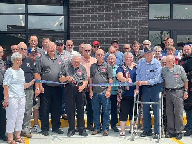 Members of LICVOA, VFW and American Legion Auxiliary members and area veterans pose for a photo during the ribbon-cutting portion of the ceremony and open house on Saturday. Edwin Allender, LICOVA president is shown cutting the ribbon.