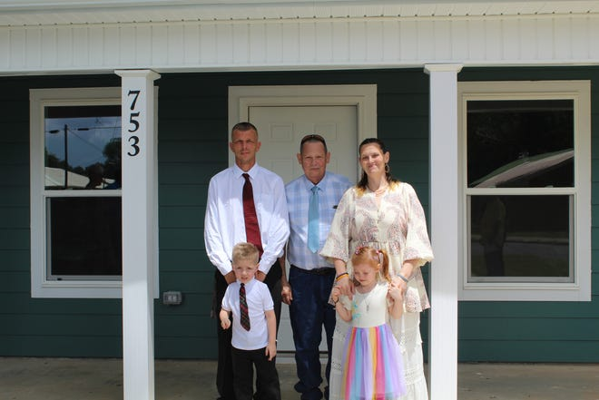 Solitair Hutchins and her family stand outside their new home in Crestview.