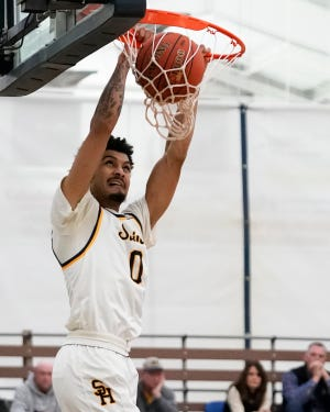 Former Siena Heights standout DeMarco Dickerson dunks during a game in the 2019-20 season.