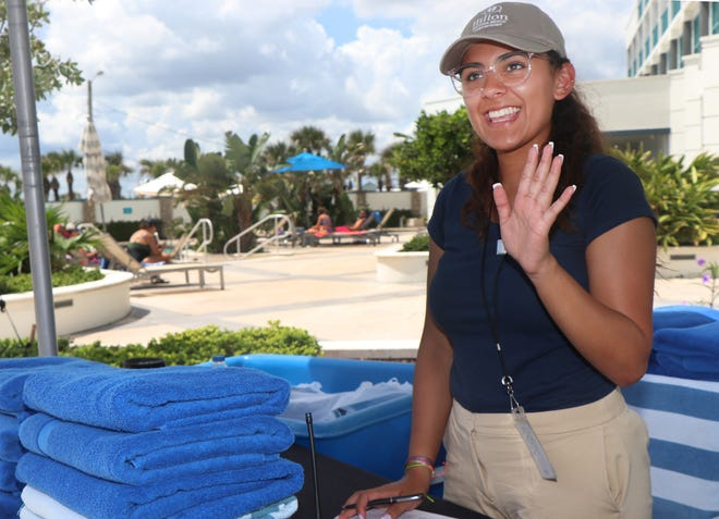 """Pool attendant Francia Gonzalez waves to an approaching guest on Monday at the Hilton Daytona Beach Oceanfront Resort. The hotel is in the midst of hiring for an assortment of jobs throughout the 744-room hotel, the area's largest. """"It's really the whole gamut,"""" said Jordan White, the hotel's Human Resources director. """"Food and beverage, reservations, people support; it's almost the whole hotel."""""""