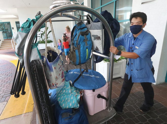 Hisa Tamura, a guest services employee, rolls a guest's luggage to their car during check-out on Monday at the Hilton Daytona Beach Oceanfront Resort. The 744-room hotel, the largest in Daytona Beach, is among the Volusia County hotels struggling to hire workers as summer tourism is booming, a reflection of a national trend.