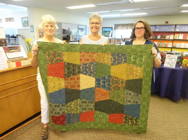 From left at the Hawley Public Libary, July 15, 2021: Susie George, Library Board President; Elaine Barnes, who sewed this quilt being raffled in honor of the library's 60th anniversary; and Amy Keane, Library Executive Director. Raffle tickets, sold at the library, are $1 each, six for $5; the drawing is set for August 31.