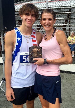 Aidan LaTourette of Honesdale was the overall winner of the 35th Annual Perkins Race, held Saturday in Dyberry Township. The cross country standout is shown here accepting his gold medal from race organizer Lindsey Pender.