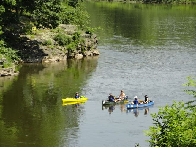Thousands of people enjoy the waters of the Upper Delaware Scenic & Recreational River every summer. This group was rounding a rocky point on the Pennsylvania side at left and was about to head under the Narrowsburg bridge, recently. The National Park Service requires wearing of life jackets when boating, swimming or wading when the river level reaches six feet.  Photo by Peter Becker