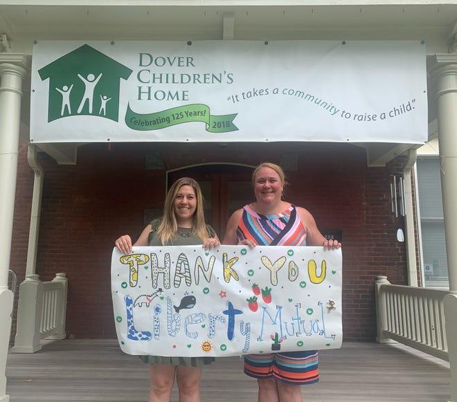 Dover Children's Home Development Director Lauren Petraitis, left, and Executive Director Renee Touhey-Childress display a handmade thank you poster from the children at Dover Children's Home.